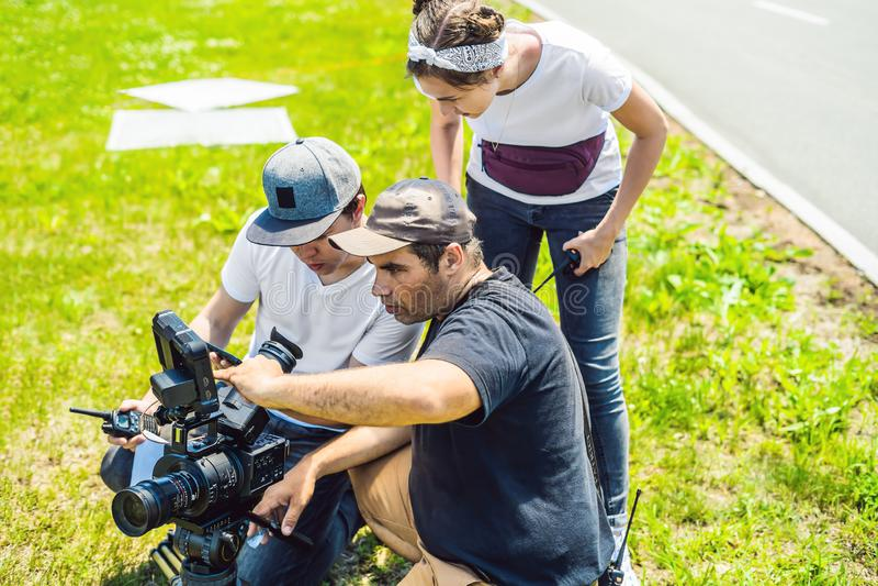 Un opérateur de cameraman discuter le processus de tir avec un directeur et un DP image stock