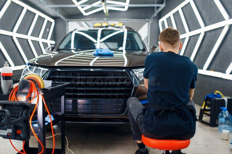 Un operaio maschio lucida la superficie dell'auto, specificando fotografie stock libere da diritti