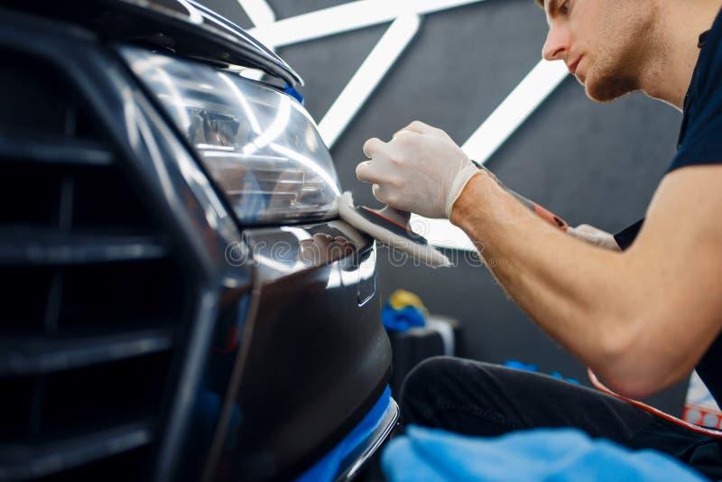 Un operaio ripulisce il paraurti anteriore, l'auto indica i dettagli immagini stock libere da diritti