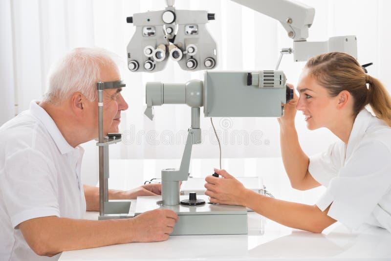 Un optometrista Doing Vision Testing per il paziente maschio fotografia stock libera da diritti