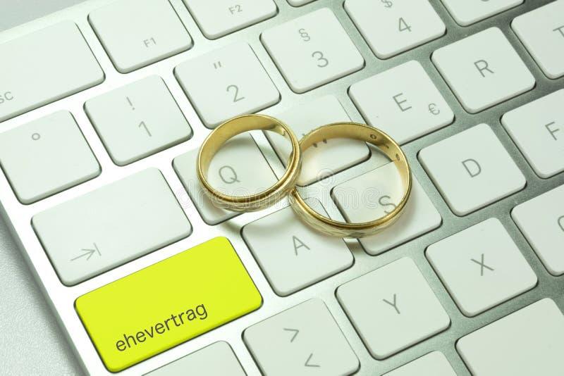 Un ordenador con un botón para un contrato de matrimonio y dos anillos de bodas imágenes de archivo libres de regalías