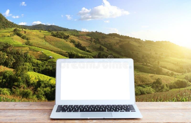 Un ordenador portátil con la pantalla blanca en la tabla de madera con la opinión hermosa del paisaje del fondo imagen de archivo