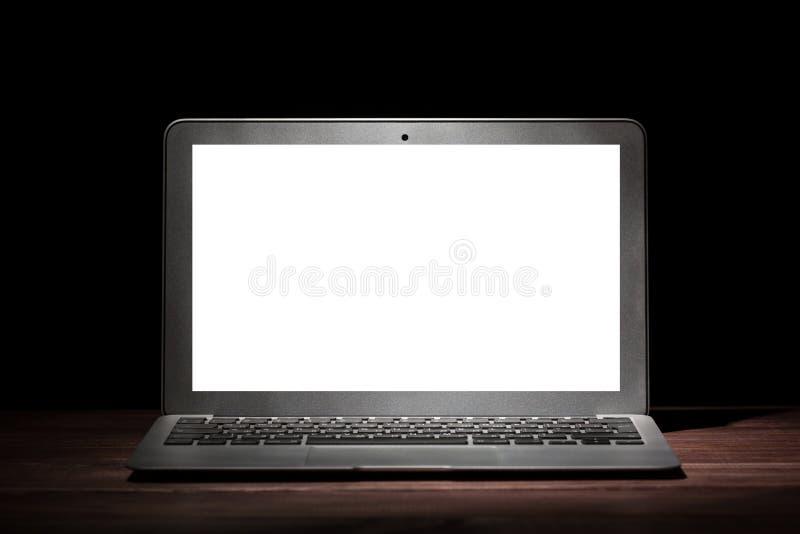 Un ordenador portátil moderno de plata con la pantalla blanca vacía en la tabla de madera en un cuarto oscuro en fondo negro Maqu fotografía de archivo