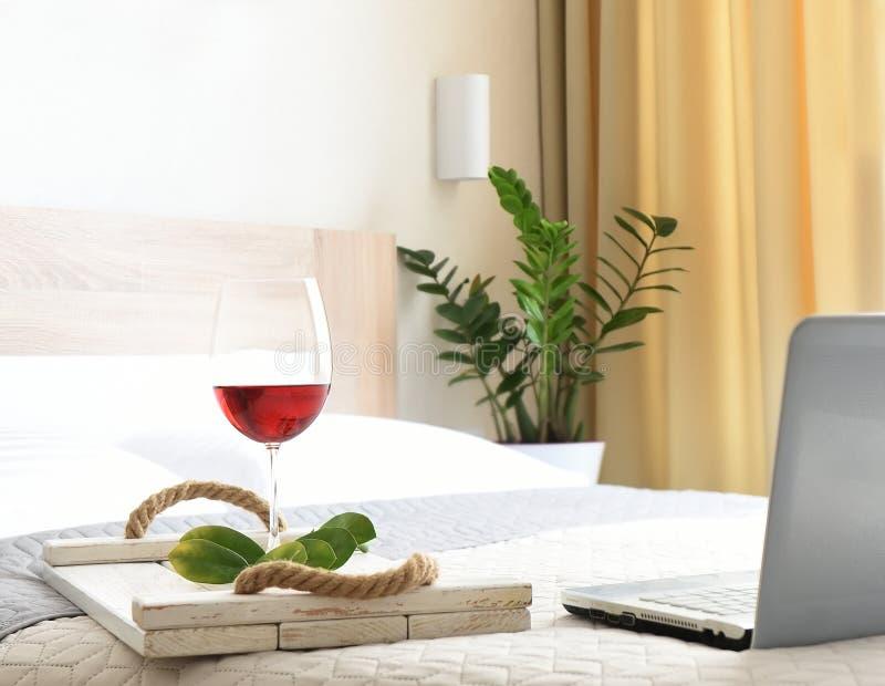 Un ordinateur portable et un plateau avec un verre de vin sur le lit Travailler à distance depuis la maison image stock