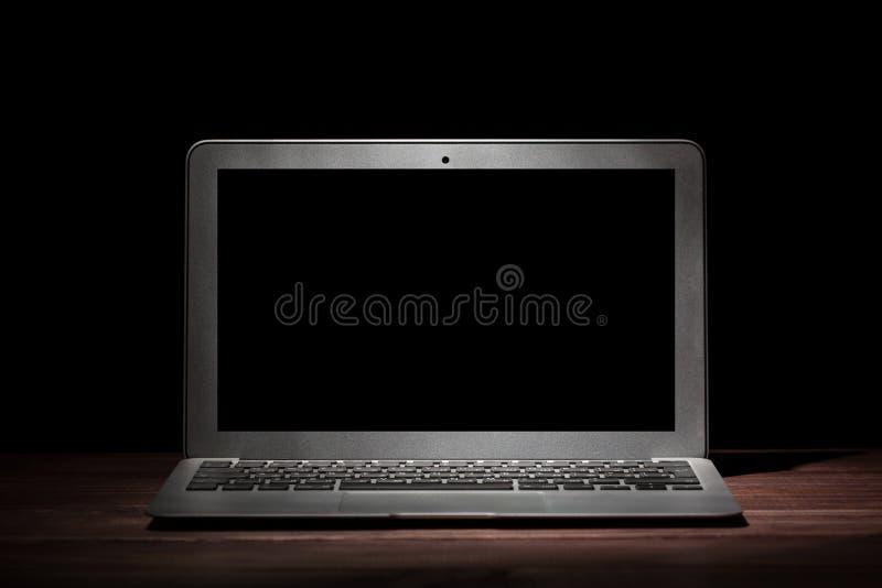 Un ordinateur portable moderne argenté sur la table en bois dans une chambre noire sur le fond noir Maquette gentille pour votre  photos stock