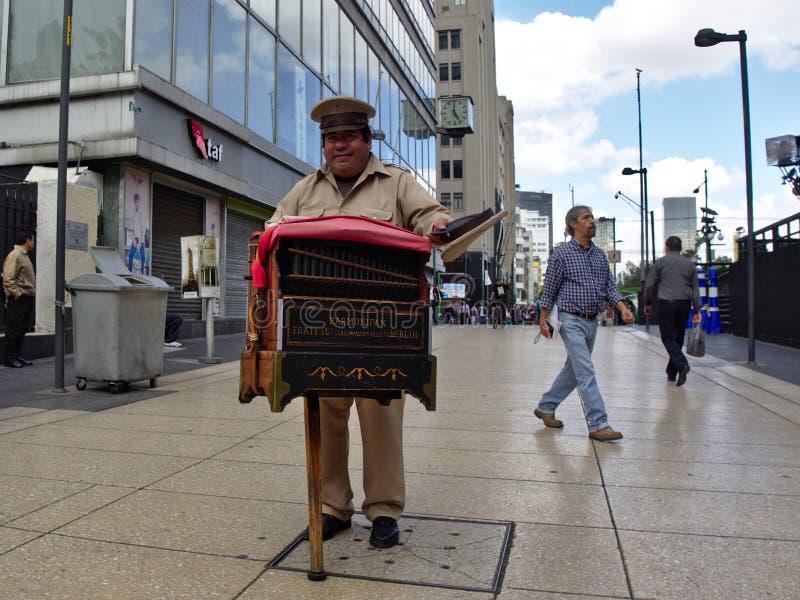 Un organillero juega música como él pide de extremidades con su sombrero imagen de archivo