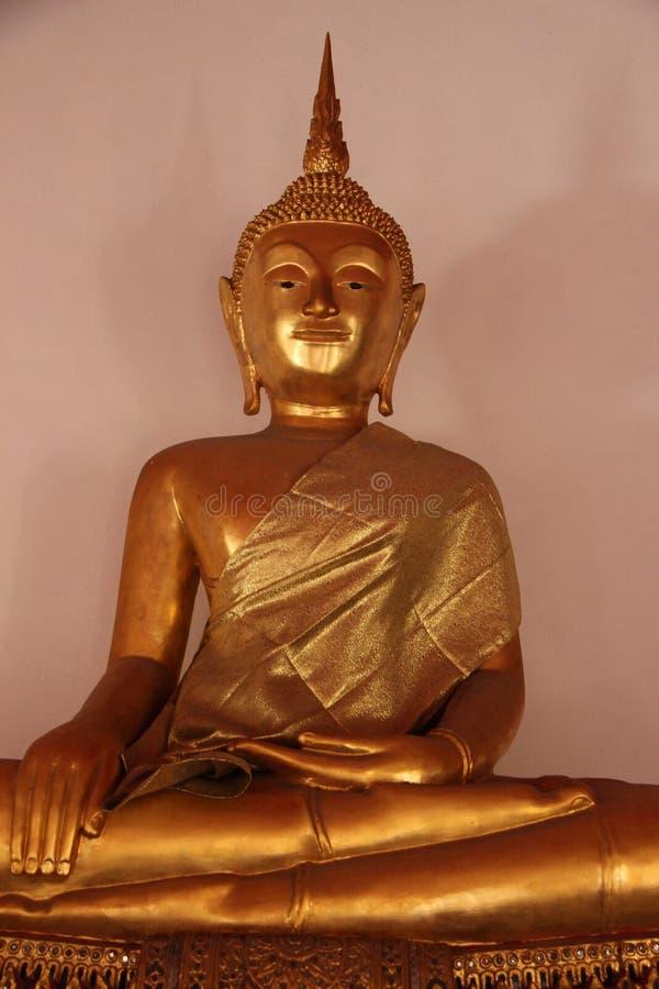 Un oro Buddhas con il fronte Seat di Mercifulness sulla base dello stucco fotografia stock