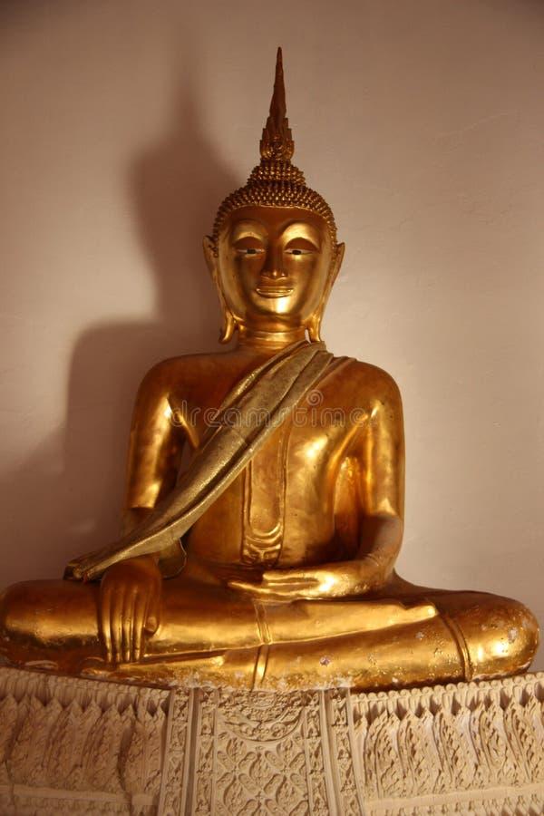 Un oro Buddhas con il fronte sorridente Seat sulla base dello stucco fotografia stock libera da diritti