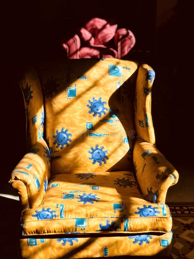 Un oro y una silla roja toman el sol en el sol y las sombras imagenes de archivo