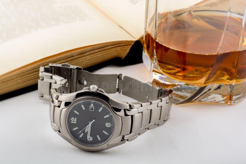 Un orologio, una bevanda e un libro fotografia stock