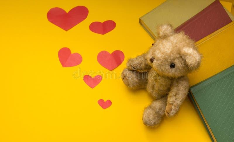 Un orsacchiotto si siede vicino ai libri su un fondo giallo dei cuori sparsi fotografia stock