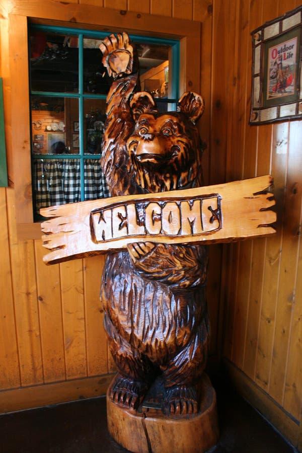 Un orso felice di legno dà il benvenuto a con l'onda della sua zampa immagine stock