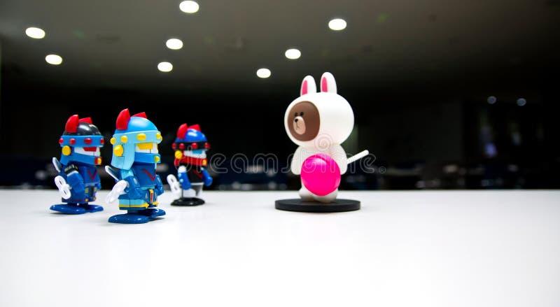Un oso blanco con un caramelo rosado en una etapa oscura del teatro sin una dice a los guardias del robot que llevan cascos azule imagenes de archivo