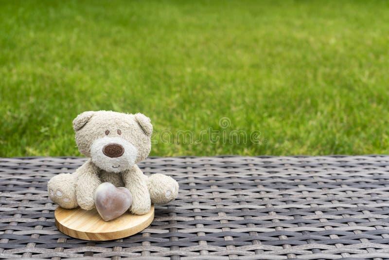 Un oso de peluche lindo que lleva a cabo el corazón marrón del chocolate con leche que se sienta en el top del práctico de costa  imágenes de archivo libres de regalías