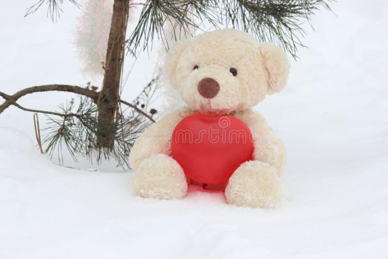 Un oso solo con un corazón rojo grande se está sentando en esperar de la nieve con amor el días de fiesta foto de archivo libre de regalías