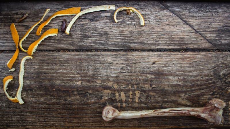Un osso rosicchiato del pollo su un bordo di legno immagini stock