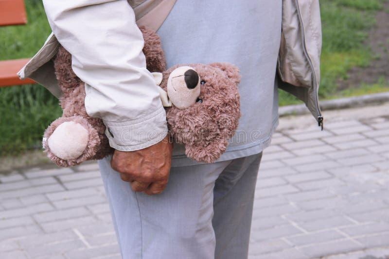 Un ours de nounours dans la main d'un homme promenade de personne âgée sur la rue Le grand-papa tient un jouet d'un enfant du ` s image stock
