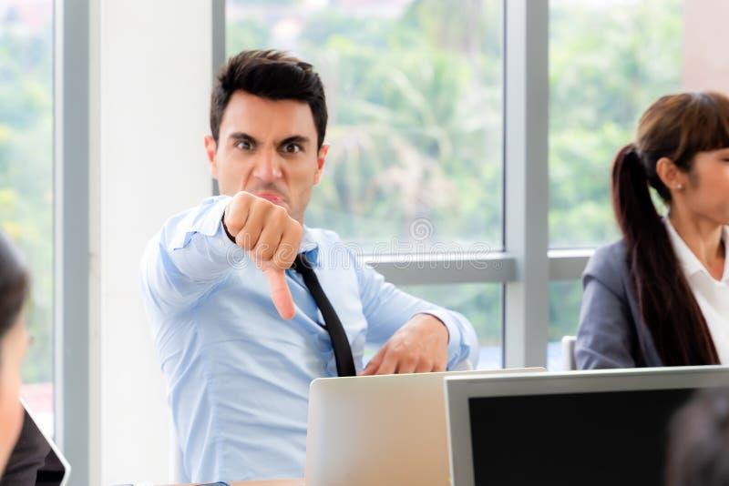 Un ouvrier montre son pouce avec un groupe de personnes dans la salle de réunion, se concentre sur la main, mauvais concept photo libre de droits