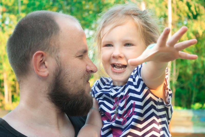 Un père avec une barbe tient une fille dans des ses bras image stock