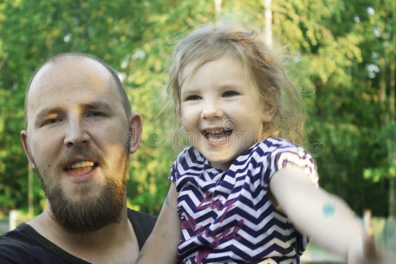 Un père avec une barbe tient une fille dans des ses bras photos stock
