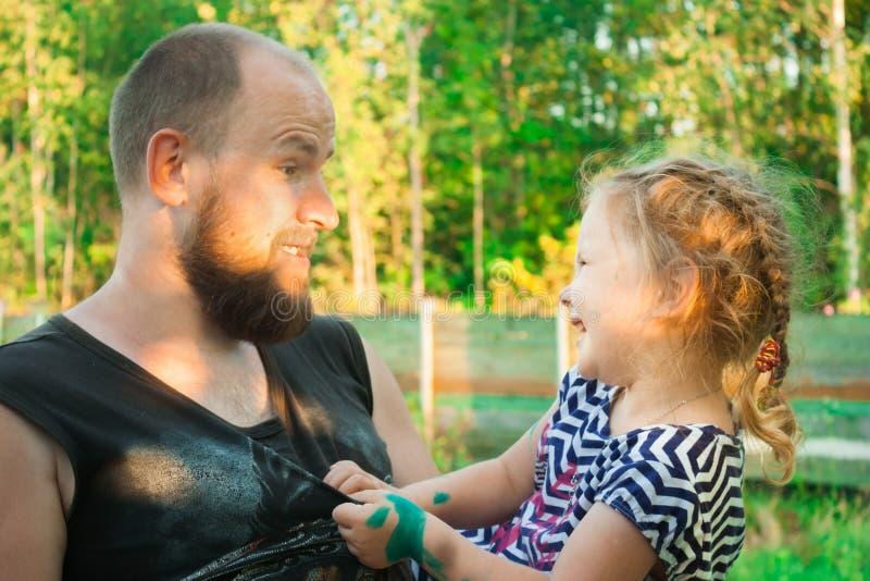 Un père avec une barbe tient une fille dans des ses bras photos libres de droits