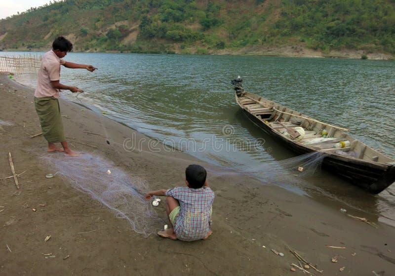 Un père et un fils démêlant un filet de pêche avant la pêche allante en rivière photos libres de droits