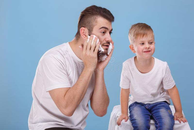 Un père et un petit fils ont l'amusement, calomnies de papa son visage avec raser la mousse Un déjeuner sec dans une cuillère photographie stock libre de droits