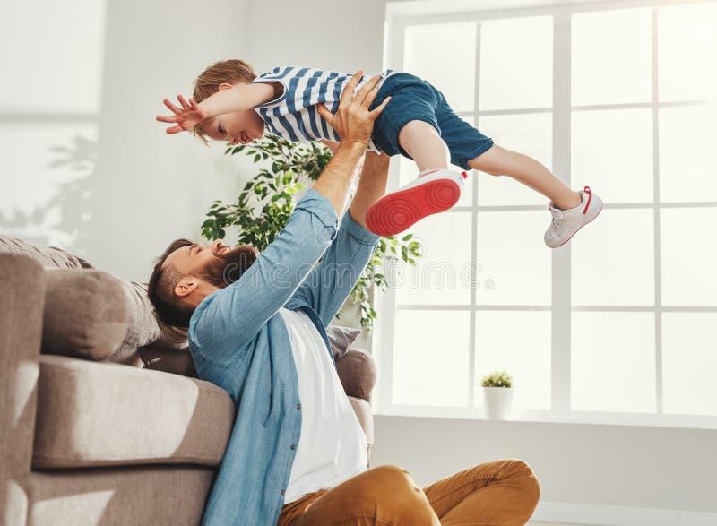 Un père joyeux qui joue avec un enfant à la maison image libre de droits