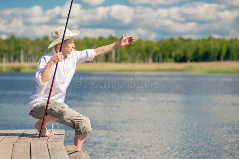 Un pêcheur dans des vêtements ruraux en voyage de pêche image stock