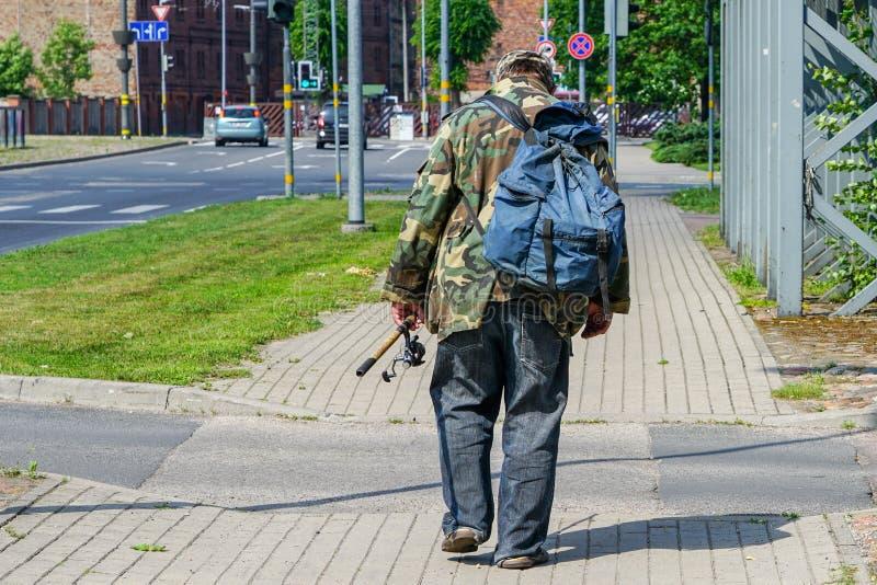 Un pêcheur ivre avec un sac à dos et une canne à pêche dans sa main descend la rue de ville photographie stock