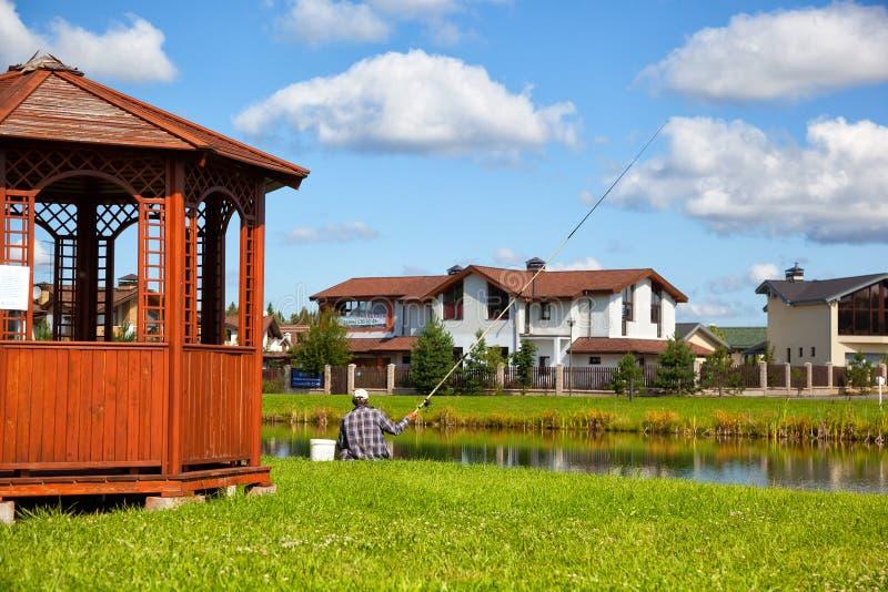 Un pêcheur pêche des poissons dans l'étang sur le territoire d'un complexe de cottage de pays photos stock