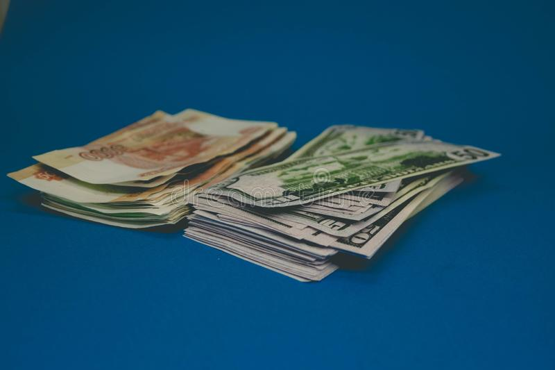 un pacchetto delle rubli russe e dei dollari due batuffoli di soldi su un fondo blu ricchezza dell'opportunità Successo fotografie stock