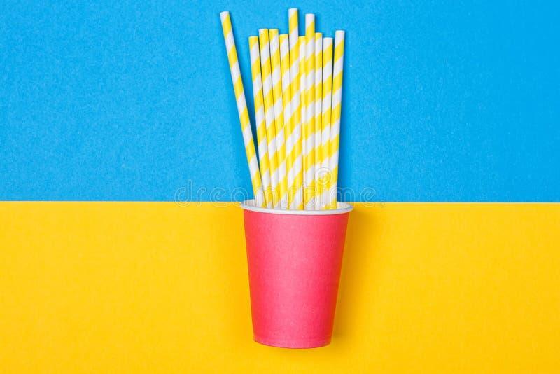 Un pacco delle cannucce colorate multi in una tazza di carta immagine stock