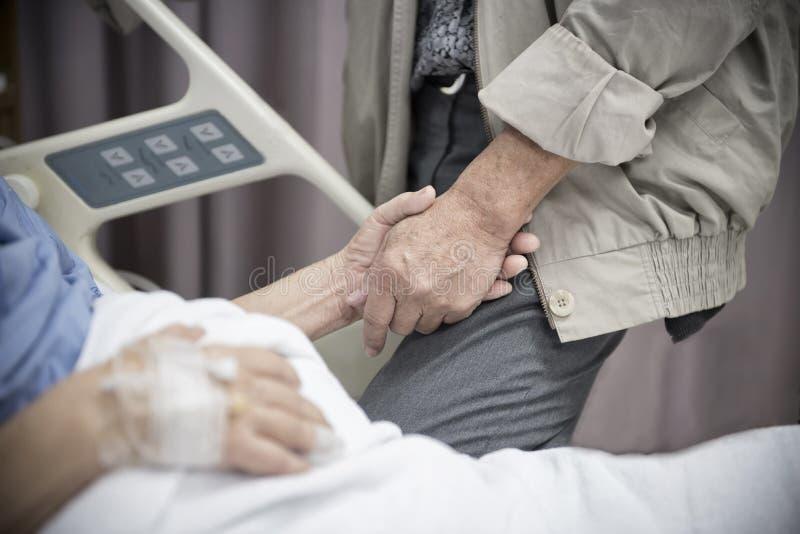 Un paciente enfermo de las mujeres mayores que miente en la cama que lleva a cabo su mano del marido en el hospital para el fondo imagenes de archivo