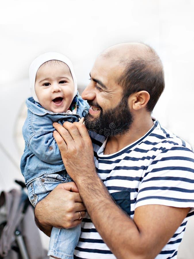 Un padre cariñoso detiene a un niño en sus brazos Foto emocional imagen de archivo