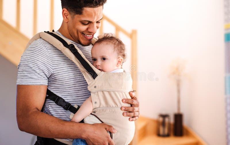 Un padre con el peque?o hijo del ni?o en portador dentro en casa foto de archivo