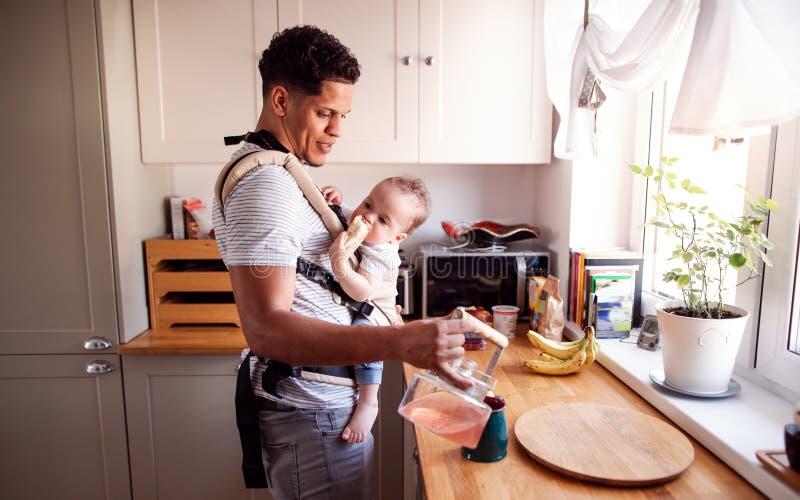 Un padre con il piccolo figlio del bambino in trasportatore in cucina all'interno a casa fotografia stock libera da diritti