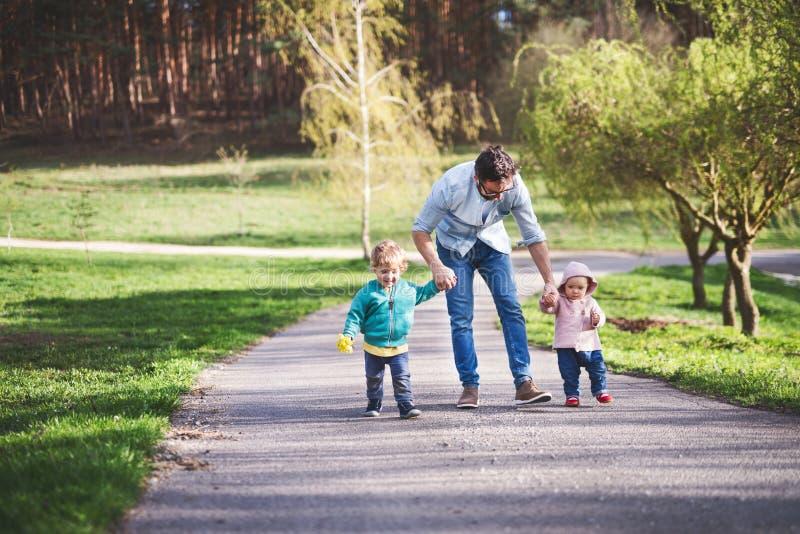 Un padre con sus niños del niño afuera en un paseo de la primavera foto de archivo