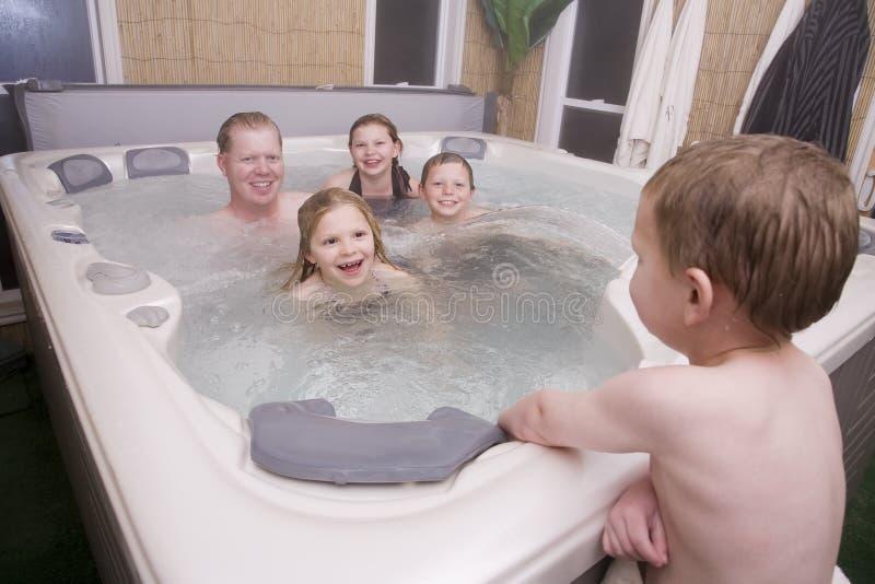 Un padre e bambini in vasca calda fotografia stock libera da diritti