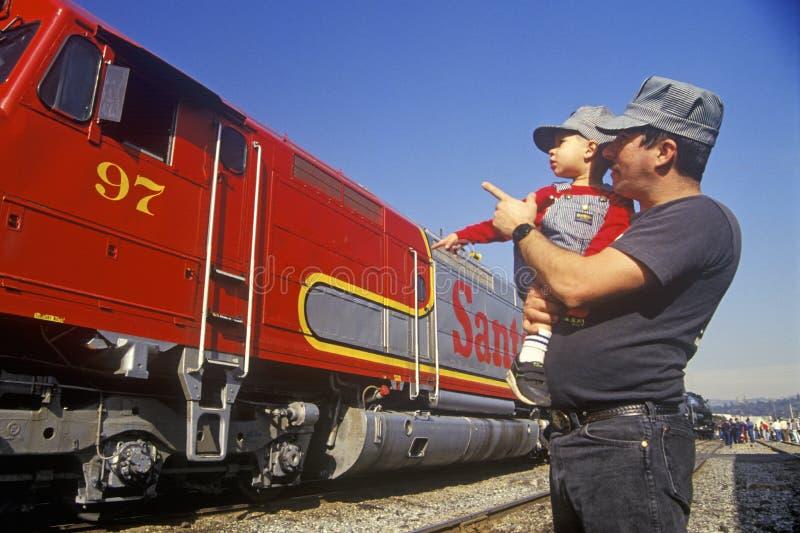 Un padre e un figlio in cappucci dell'ingegnere esaminano un treno diesel storico di Santa Fe a Los Angeles, CA fotografie stock libere da diritti