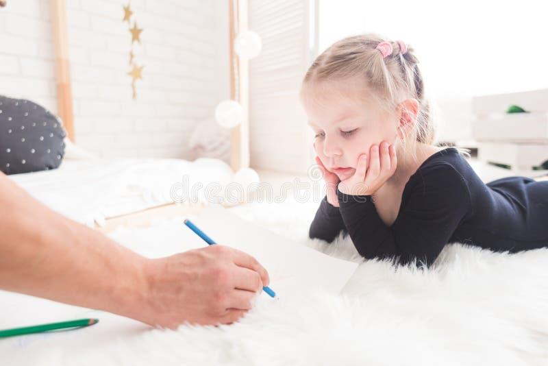 Un padre joven y su mentira de la hija en el piso y drenaje con los l?pices coloreados foto de archivo