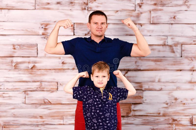 Un padre joven y una demostración de ocho años del hijo el poder de músculos hombre y muchacho elegantes imagen de archivo