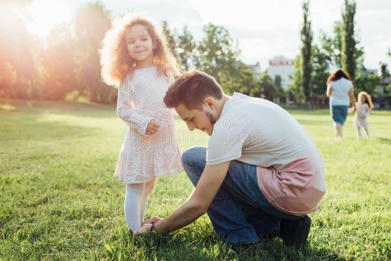 Un padre que ayuda a su pequeña hija con sus zapatos en el parque Muchacha rizada linda del niño en vestido hermoso imagenes de archivo