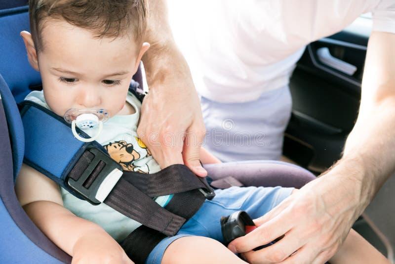 Un padre que pone a su pequeño hijo en su asiento de carro Él está llevando la ropa informal y está mirando a su hija Protección  foto de archivo