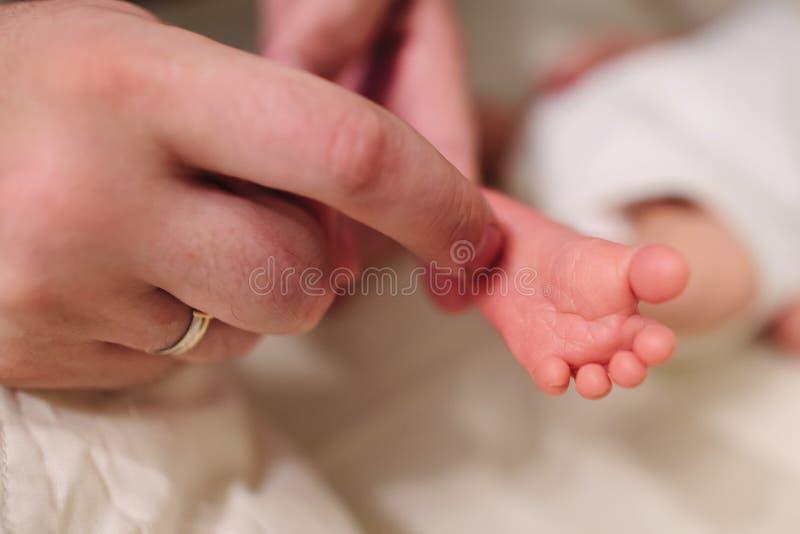 Un padre segna un tallone del ` s del neonato fotografia stock libera da diritti
