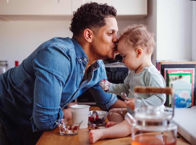 Un padre y un peque?o hijo del ni?o que comen la fruta y el yogur dentro en casa fotos de archivo libres de regalías