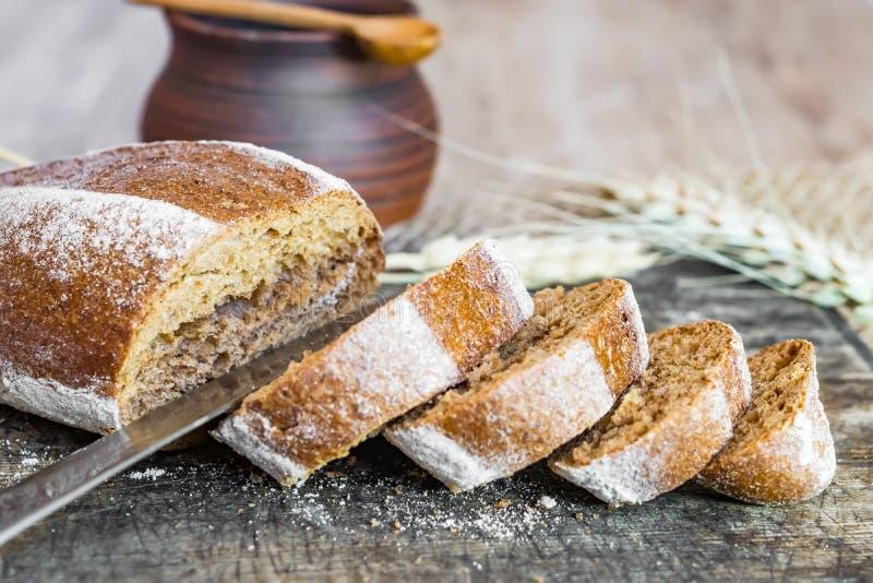 Un pain de forme ovale de pain de seigle et de tranches coupées sur le vintage de conseil en bois, style rustique, gâteaux faits  images stock