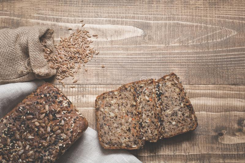 Un pain de pain de seigle entier rustique frais de repas, coupé en tranches sur un conseil en bois, fond rural de nourriture image stock