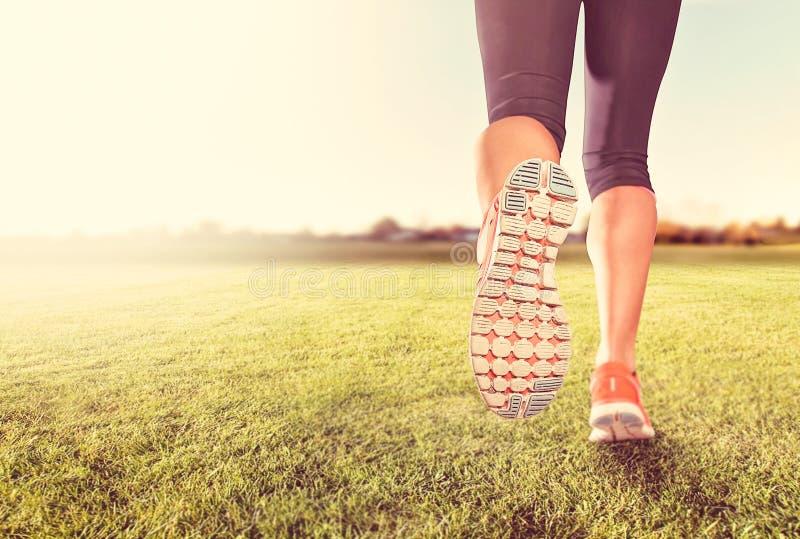 Un paio atletico delle gambe su erba durante alba o il tramonto immagine stock libera da diritti