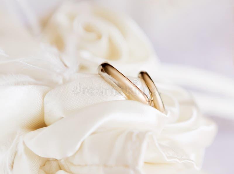 Un paio degli anelli di oro di nozze su un cuscinetto immagine stock libera da diritti